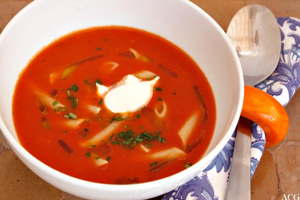 Serveringsklar tomatsuppe med pasta og creme fraiche