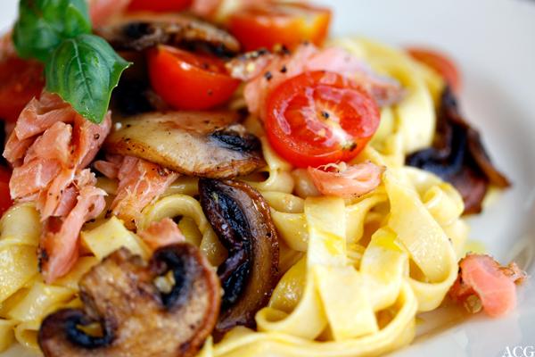 nærbilde av båndspaghetti, laks og sopp