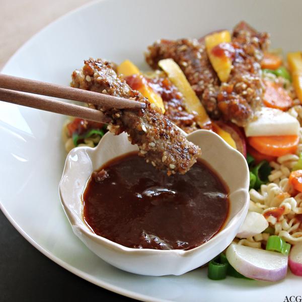 Nærbilde av spisepinner med sprøstekt biffkjøtt og sursøt mangosaus