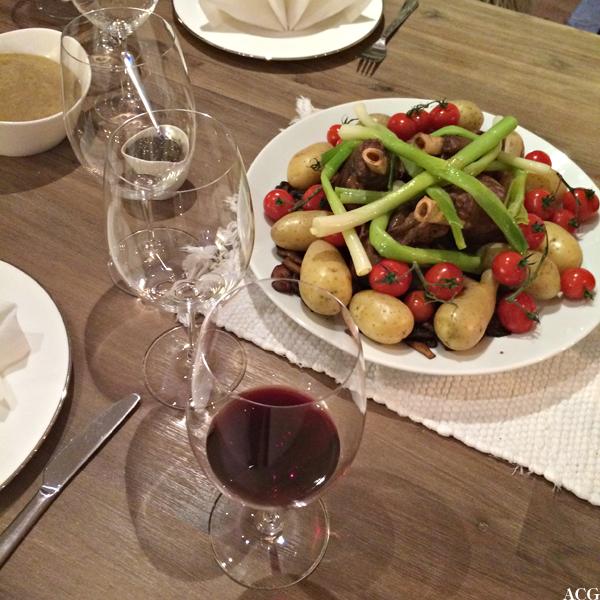 Dekket bordt mes lammeskank på fat og rødvin i glass