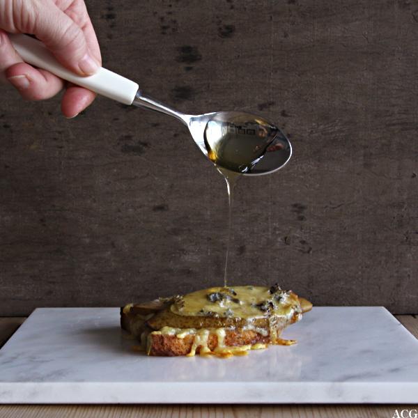 Bilde av en skje med honning som dryppes over et ostesmørbrød med pære og blåmuggost