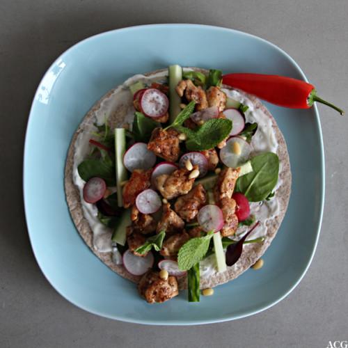 BIlde av fullkornstortilla med kylling og salat på blå tallerken