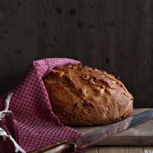 Rundt brød på fjøl med kjøkkenhåndkle over seg og en brødkniv i forkant