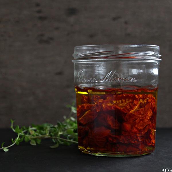glass med tørkede tomater i olje og en kvist timian