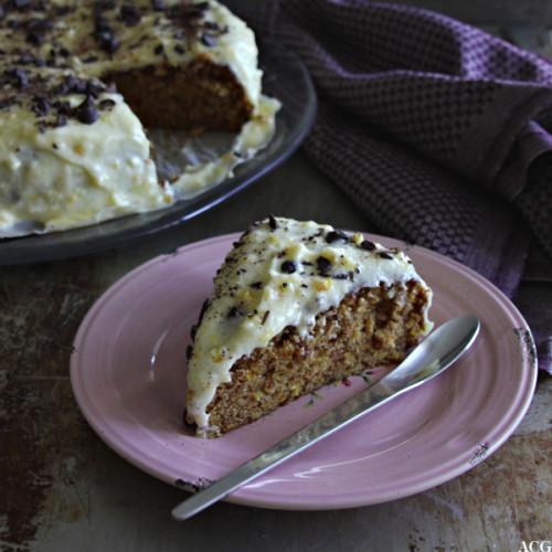 et stykke appelsinkake med hele kaken i bakgrunnen